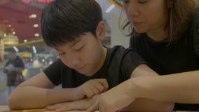 Zeitlupe 4K des asiatischen netten Jungen mit Mutterlesemenübuch und -punkt Glückliches Gesicht stock video