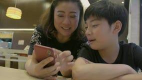 Zeitlupe 4K des glücklichen asiatischen Jungen und seiner der Mutter, die am intelligenten Telefon, mit Lächelngesicht aufpasst stock video footage