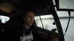 Zeitlupe-Mann transportiert Leute mit dem Fahrzeug entlang nasser Straße stock footage