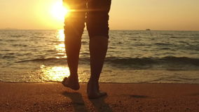 ZEITLUPE: Mannweg bei Meer und Sonnenuntergang stock video