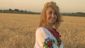 Zeitlupe, Nahaufnahme, nette Frau im nationalen Kostüm, das auf Weizen-Feld aufwirft stock video footage