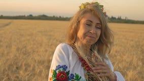 Zeitlupe, Nahaufnahme, Schönheit im nationalen Kostüm auf den Weizen-Feld-Pressen zum Kasten des Weizens stock footage