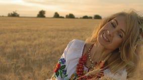 Zeitlupe, Nahaufnahme, Schönheit im nationalen Kostüm auf Weizen-Feld schaut Weizen-Spitzen in den Händen und im Lächeln stock video footage