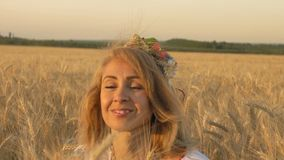 Zeitlupe, Nahaufnahme, Schönheit im nationalen Kostüm sitzt an den Weizen-Sprösslingen auf Feld stock footage