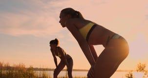 ZEITLUPE, NIEDRIGER WINKEL, ABSCHLUSS OBEN, SONNEN-AUFFLACKERN: Athletisches Mädchen, das Strandvolleyballsprünge in der Luft und stock footage