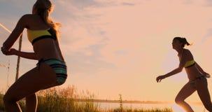 ZEITLUPE, NIEDRIGER WINKEL, ABSCHLUSS OBEN, SONNEN-AUFFLACKERN: Athletisches Mädchen, das Strandvolleyballsprünge in der Luft und stock video