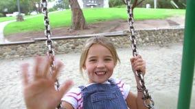 Zeitlupe-Reihenfolge des Mädchens auf Schwingen beim Spielplatz-Wellenartig bewegen stock video