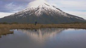 Zeitlupe - Reisender, der Queransicht zum taranaki Vulkan in der Nordinsel von Neuseeland und mit wlking ist stock video