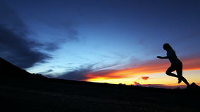Zeitlupe-Schattenbild-Paare, die bei Sonnenuntergang laufen