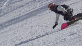 Zeitlupe schoss vom professionellen männlichen Snowboarderreitensnowboard, der extreme Bremsungen auf schneebedecktem Gebirgshüge stock video
