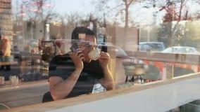 Zeitlupe schoss von einem Mann, der im Café mit einem Smartphone in den Händen sitzt stock video footage