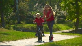 Zeitlupe schoss von einer jungen Frau, ihrem kleinen Sohn beizubringen, wie man Fahrrad fährt stock footage