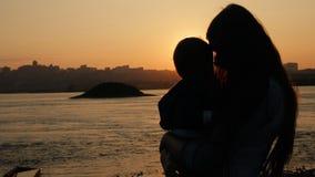 Zeitlupe schoss von einer jungen Mutter, die ihren kleinen Sohn küsst, der den Fluss bei Sonnenuntergang bereitsteht stock video footage