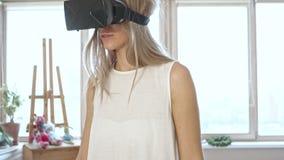 Zeitlupe von Blondinen in versuchenden Gläsern der virtuellen Realität des Leerraumes stock video