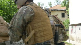 Zeitlupe von den Soldaten der besonderen Kräfte, die von ruiniert speichern und tragen, einen verletzten Kameraden errichtend stock footage