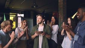 Zeitlupe von Schlagkerzen des hübschen bärtigen Mannes auf Geburtstagskuchen an der Büropartei mit den Kollegen, die Hände klatsc stock footage