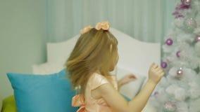 Zeitlupeansicht des glücklichen kleinen Mädchens in werfendem Kissen des Schlafzimmers an der Kamera stock video