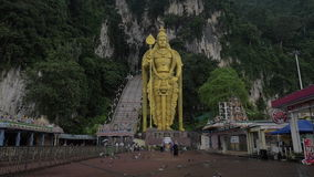 Zeitlupeclip von Fliegentauben auf Vordergrund- und Murugan-Goldstatue gegen Felsenwand, Gombak, Selangor, Malaysia stock footage