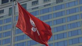 Zeitlupeflagge von Hong Kong wellenartig bewegend in den Wind mit modernem Wolkenkratzer stock footage