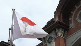 Zeitlupeflagge von Japan wellenartig bewegend in Wind Tokyo-Station, Bahn-Marunouchi stock video