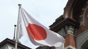 Zeitlupeflagge von Japan wellenartig bewegend in Wind Tokyo-Station, Bahn-Marunouchi stock video footage