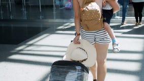 Zeitlupegesamtlänge der hinteren Ansicht der Schönheit den kleinen Jungen halten, der mit Koffer im Flughafenabfertigungsgebäude  stock footage