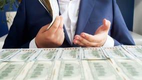 Zeitlupegesamtlänge des erfolgreichen burinessman sitzend am Schreibtisch bedeckt mit Geld und großen Stapel US-Dollars halten stock video footage