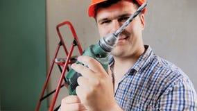 Zeitlupegesamtlänge des jungen Vorarbeiters im Hardhat unter Verwendung der elektrischen Bohrmaschine am Haus unter Erneuerung stock video