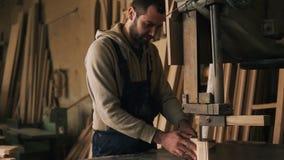 Zeitlupegesamtlänge des Tischlers arbeitend mit einem hölzernen Block in der Werkstatt Elektrisch sah Holzmöbel hinten stock footage