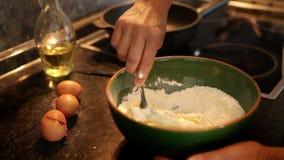 Zeitlupegesamtlänge eines mischenden Mehls des Kochs mit den Eiern, zum des Teigs für Pfannkuchen zu machen stock video footage