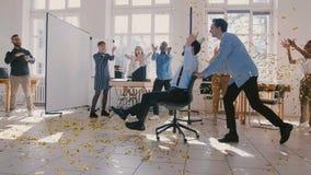 Zeitlupegeschäftsleute feiern Erfolg zusammen, Klatschen zur männlichen Cheffahrt in den Bürosiegerstuhl-Schießenkonfettis stock video