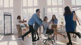 Zeitlupegeschäftsleute feiern Teamerfolg, Klatschen zum weiblichen Chefreitsiegerstuhl entlang großem modernem Büroflur stock video