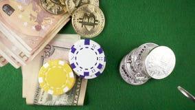 Zeitlupemünzen fallen unten auf Chips und Geld auf einer Tabelle mit bitcoins Draufsicht stock video footage