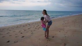 Zeitlupemutter und kleine Tochter, die an der Ankunft zur Küste sich freuen stock video