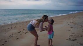 Zeitlupemutter und kleine Tochter, die nahe Meer am Abend gehen stock footage