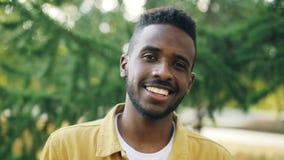 Zeitlupenahaufnahmeporträt des netten Afroamerikanermannes, der draußen Kamera lächelt und betrachtet Schöne Natur stock footage