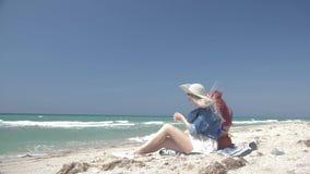 Zeitlupepaare von den jungen sexy Frauen, die in boho Art gekleidet werden, sitzen auf einem sandigen Strand mit Handys stock footage