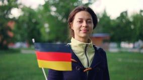 Zeitlupeporträt der netten jungen Frau, die offizielle deutsche Flagge wellenartig bewegt und Kamera bei der Stellung in nettem b stock video