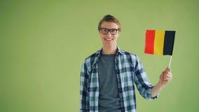 Zeitlupeporträt der wellenartig bewegenden Flagge des jungen Mannes von Deutschland und von Lächeln stock footage