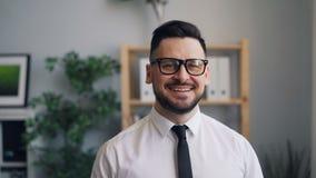Zeitlupeporträt des Geschäftsmannes Kamera betrachtend und im Büro lächelnd stock video