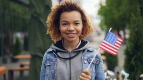 Zeitlupeporträt des hübschen Afroamerikanermädchenjugendlichen, der Kamera betrachtet und herein stehende Außenseite US-Flagge hä stock footage