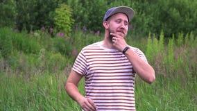 Zeitlupeporträt des jungen bärtigen lustigen Mannes mit OKAYhandzeichen der Kappe stock footage