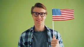 Zeitlupeporträt des jungen Mannes mit dem amerikanischen Staatsflaggelächeln stock footage