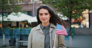 Zeitlupeporträt schöner Mädchenholding amerikanischer Flagge, die draußen lächelt stock video