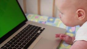 Zeitlupeporträt von 6 Monate alten Baby, die mit Laptop in seinem Bett spielen stock video
