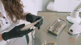 Zeitlupeschießen steadikam Frauenzahnarzt hält einen Zahnarzt in seinen Händen, überprüft Brauchbarkeit, sich vorbereiten zu entf stock footage