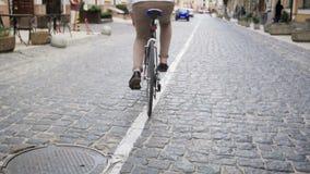 Zeitlupevideo des Reitens des jungen Mannes auf Sportweinlesefahrrad auf gepflasterter Straße stock video