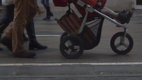 Zeitlupevideo von unerkennbaren Leuten mit Kinderwagen in der Straße stock footage