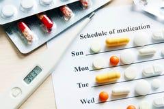 Zeitplan der Medikation für eine Woche mit verschiedenen Pillen und Thermometer Lizenzfreie Stockfotos