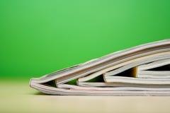 Zeitschriften, die auf Tabelle liegen Stockbilder